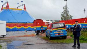 en äldre man står utanför ett cirkustält på en regning sandplan med cirkusbilar i bakgrunden