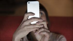 Nainen tuijottaa älypuhelinta.