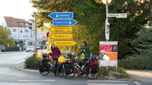 Två cyklister står framför några gula vägskyltar i Tyskland. Deras cyklar är fullastade med väskor. De ser glada ut. Den ena pekar på skyltarna.