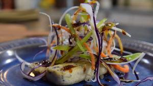 Annos paistettua tofua kera teriyakikastikkeen ja juuressalaatin kanssa lautasella.