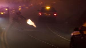 En polisman använder sin pistol för att skjuta av en elledning på en landsväg
