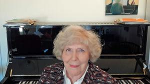 Pianisti Meri Louhos kotonaan pianon edessä, taustalla hänen maalamansa taulu pianistista