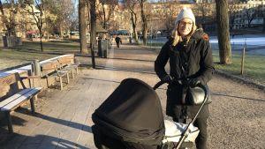 Maria Kjell-Andrén utomhus med en barnvagn.