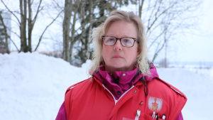 En kvinna med glasögon och axellångt blont hår står utomhus vid en snöhög. På sig har hon en röd Röda Korset-väst.