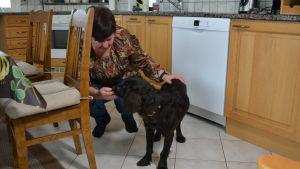 Christel Holmlund-Norrén tillsammans med hunden Saga hemma i köket i Norra Vallgrund, Korsholm.