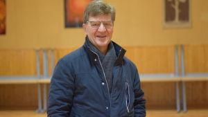 En glasögonprydd man står inne i en tom sal i ett föreningshus.