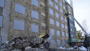 Lyftkran vid ett hus med nedriven fasad