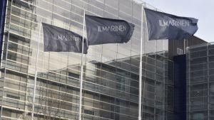 Flaggor vajar utanför ett glashus.