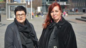 Två kvinnor står på ett torg och tittar in i kameran.