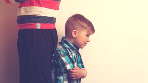 en liten pojken står med ryggen vänd mot sin förälder. Han ser arg ut.