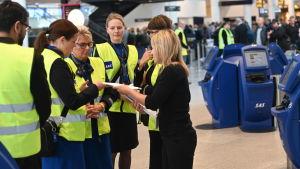 SAS kabinpersonal i gula västar tar emot instruktioner på en flygplats.