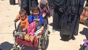 Två små barn sitter i en sliten smutsig rollstol.