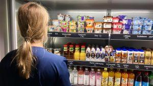 En kvinna står framför ett kylskåp och väljer bland mat och drycker i en restaurang.