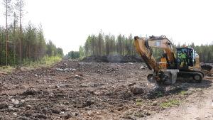En grävmaskin gör markarbeten vid ett skogsområde i Närpes.