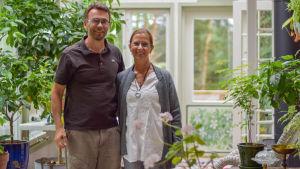 En man och en kvinna inne i en glasveranda där det finns blommor.