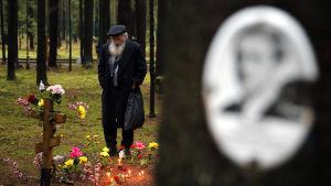 Gammal skäggig rysk man betraktar en släktingsgravkors i skogen. I förgrunden på ett träd ett oskarpt foto på en kvinna..