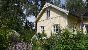 En bild på en trädgård med massa blommor och ett gult hus.