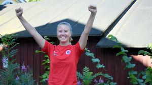 Porträttbild på Ida Adamsson med händerna i luften av lycka.