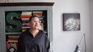 Författaren Sanna Tahvanainen framför sin bokhylla.