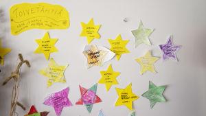 En bild på stjärnor på en vägg där önskningar har skrivits ut