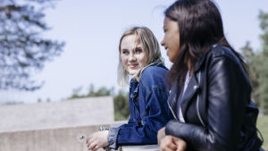 två flickor lutar sig mot en mur