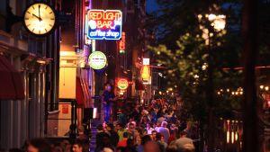Nattlig bild med folkmassor som vandrar längs sexstråket i Amsterdam