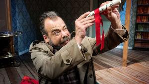 """Skådespelaren Max Forsman kikar in i ett hoprullat papper som det står """"Testamente"""" skrivet på."""