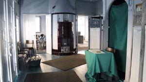 En förmak med kakelugn, flera dörrar och ett grönt bord och skynke.