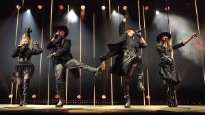 Fyra sångare klädda i svarta scenkläder dansar på en dramatiskt upplyst scen.