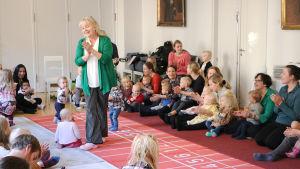 En kvinna står upp i en cirkel av föräldrar och barn som klappar i händerna.