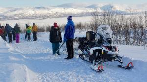 Snöskoter och ett gäng med längdskidåkare i den svenska fjällen.