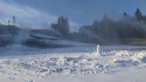 Vintern 2020 var snöfri ända till februari. Vid Hirvensalo skidbacke i Åbo skjuter snökanoner snö en solig vinterdag.