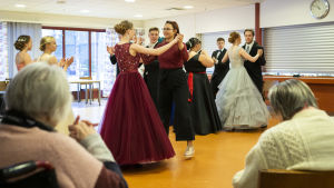 Etualalla vanhuksia selin. Taustalla nuoret tanssivat juhlapuvuissaan.
