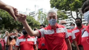 Lee Hsien Yang i ansiktsskydd kampanjerar i ett folkhav i Singapore.