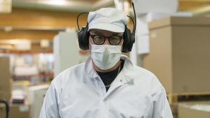 En medelåldersman i vita skyddskläder, munskydd och hörselskydd.