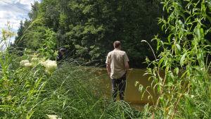 en man som står vid vattenbrynet.