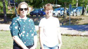 Två kvinnor står på ett soligt gräsplan. Bilar i bakgrunden. Sommar. De ler.