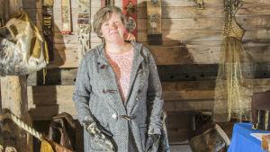 Bild på Anita Storm vid sitt utställningsbord med olika hantverk i leder och päls.