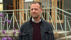 en medelåldersman i svart jeansjacka och brunt kort hår.