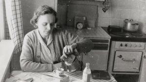 Svartvitt foto av Sirkka- Liisa Miettinen som häller upp kaffe åt sig själv sittande vid köksbordet.