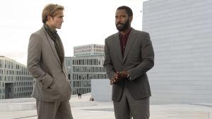 Protagonisten och hans vapendragare Neil står kostymklädda i en anonym storstadsmiljö.