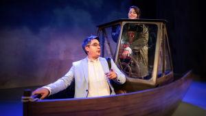 En kvinna styr och en man sitter i en båt på en teaterscen.