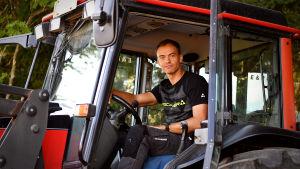 Perttu sitter bakom ratten i traktorn och tittar ut genom dörren