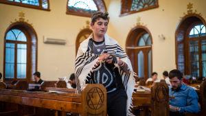 En judisk pojke ber inne i en synagoga i Quba i Azerbajdzjan.