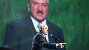 Aleksandr Lukasjenko står i en talarstol och pekar framåt med ett finger. I bakgrunden ett stort fotografi på honom. Den 17 september 2020.