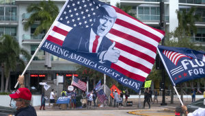 Demonstrant med Trump-flagga utanför tv-huset i Miami där Trump svarade på frågor som en del i kampanjen.