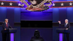 Två män står vid sina podium och debatterar.
