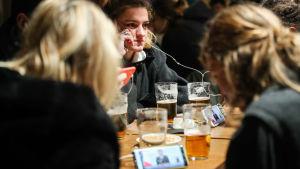 Ett gäng kvinnor sitter i en bar i Paris med halvdruckna öl på bordet framför sig. De håller upp sina mobiler och tittar och lyssnar på Macrons tal om en ny nedstängning.