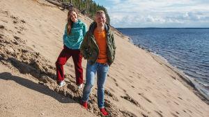 Kvinna och man står på brant sandbank med sjö i bakgrunden.