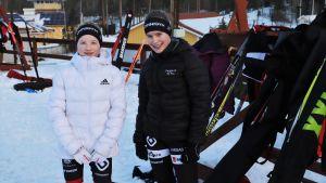 Två flickor står framför en ställning med skidor.